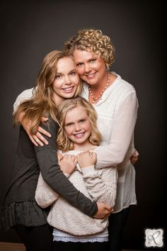 The connection between this mom and her daughters is emphasized by how they are holding each other.