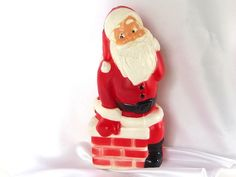 This vintage lighted hollow plastic Santa in chimney is a blow mold Christmas decoration. Featuring the Jolly Old Elf himself climbing into the chimney.