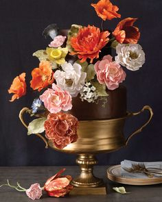 The Inspiration: The hyper-realistic botanical still-life paintings of Dutch artist Rachel Ruysch, circa 1685 to 1750 More than one guest will do a double take at the sight of this cake, which looks like a lush floral centerpiece. Custom-made sugar flowers, created by Amy DeGiulio of Sugar Flower Cake Shop in New York City, were planted in a bed of chocolate-fondant-covered cake, which was set in a large gold urn. Fill the cake's layers with rosewater buttercream to call out its blooming…