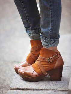 Rendering Suede Clog | Open toe strappy leather clogs. Crisscross ankle straps with brass buckles sit atop of contrasting leather with perforated design. Grainy wooden heels with comfortable padded insoles and treaded rubber soles.