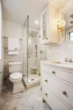 This gorgeous marble clad bathroom features a small seamless glass steam shower fitted with a marble shower surround holding a polished rain shower head on a wall adjacent to a tiled niche positioned above a corner ledge.