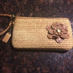 Coach Coach straw wristlet. It has a water stain inside and the clip has some wear. Overall in good condition. Coach Bags