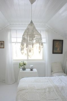 A relaxing space with a dreamy sensibility. Note the croched bedcovering and the lace covered light fixture. Very nice touches.