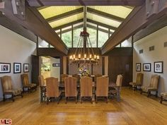 This mid-century modern has wood flooring, exposed steel structure, gabled translucent ceilings, high-back chairs, medieval circular hanging light fixture and gallery walls.
