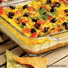7-Layer Mexican Dip Recipe: Layer in 9x13 pan... 16oz. Refried beans -- 2c. Sour cream & 1pkg. Taco seasoning -- 2 pitted, peeled, mashed avocado, 2t. Lemon juice, 3cloves garlic, minced -- 2c. Shredded cheddar cheese -- 4 diced green onions -- 1/4c. Sliced olives -- 1 diced tomatoes