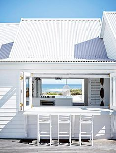 white patio bar with white stools and view of the ocean / sfgirlbybay