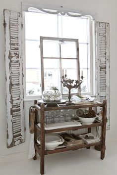Chippy shutters frames this vintage wooden cart of kitchenware ~ Favorite linens and dishes displayed and look great!