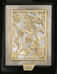 A Boucheron, Paris Retro bi-metal powder compact, the rectangular silver case with hob-nail and reed decoration, the front inset with a gold-fronted and ruby panel pierced and engraved with butterflies and flowers, signed, in a slip case.