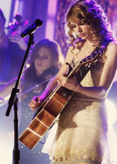 Taylor Swift...She's Known More For That Voice & Her Tendency To Write A Song About Every Guy She Dates, But Swift Is A Good Guitarist Too...Mostly Acousticlly Led, But She Does Pick Up An Electric Model In Her Stage Show Every So Often...