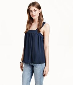 Wide-cut, sleeveless top in gently creped, woven fabric. Wide shoulder straps, foldover edge at top, and concealed fastening at back.