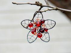 Květ. Drátovaná brož. Brož ve tvaru květu jsem vyrobila z černého drátu a skleněných perlí...čirých, červených, růžových. K přichycení slouží černý zavírací špendlík. Velikost: 8 x 8 cm Ošetřena antikorozním sprejem. Návod na údržbu bude přiložen. Originál RoníkoVo.