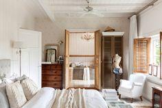 Dormitorio con baño en suite, cómoda antigua, butaca y ropa de cama de lana D00409028