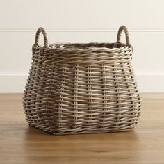 Shop Birney Round Grey Rattan Basket.  Grey-tinted rattan crafts a deep, round basket, textured with a loose weave and topped with handles.  Large and lovely, the basket is perfect for storing toys, towels, sports equipment or magazines.