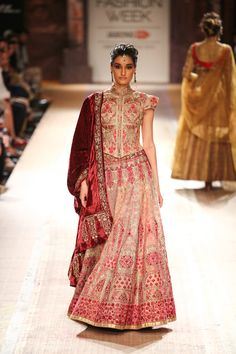 Royal red lengha by Anju Modi. Love the v shape at the end of the choli, the quaint sleeves and the velvet drape! Lakme Fashion Week 2014