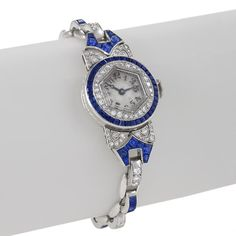 An American Art Deco platinum watch with diamonds and sapphires by Oscar Heyman. The watch has 93 round diamonds with an approximate total weight of 1.60 carats, and calibre and fancy cut sapphires with an approximate total weight of 3.60 carats.  The watch is composed of a hexagonal shaped dial which sits in a circular diamond and sapphire set case.  The bracelet strap is further set with 23 alternating links of calibre sapphires and round diamonds with strong Art Deco designed strap…