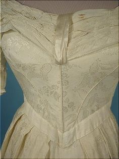 """#5096 - c. 1837-1840 Cream Silk and Linen Wedding or Evening Gown with Satin Trim!  So sweet! But as pretty as this is, you won't be able to wear it unless you have the body of a 10-year-old (ish).  So it's great for display!!  And as you see... pretty as a picture!  Worn off the shoulders for a gorgeous neckline.  """"V"""" waistband, puffed sleeves below a pleated upper arm covered with matching ecru satin band, horizontal pleated upper bodice are all elements from the late 1830s."""