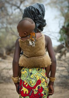Mukubal Girl Carrying Her Brother in a Dik Dik skin,  Angola Africa | Every baby in Mucubal tribe wears this piece of wood and shells in the back,  Ombeleketha. It is a kind of talisman the mother puts. Once the baby can walk, they remove it and keep it for the next baby to come!  Mucubal (also called Mucubai, Mucabale, Mugubale) people are a subgroup of the Herero ethnic group, which means they are bantu speaking, and are supposed to have come from Kenya and to be relate...