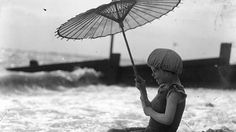Circa 1920: A child on a beach under a parasol. (General Photographic Agency/Getty Images)