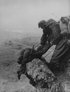 Soldiers from the Prinz Eugen Division help each other in climbing a mountain rock in the Dinaric Alps, Croatia in 1943.