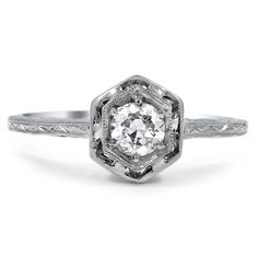 This intricate Edwardian-era ring showcases a double hexagonal frame encompassing a striking old European cut diamond. Milgrain and engraving embellish the petite shank while the gallery is pierced with unique shapes (approx. 0.35 total carat weight).