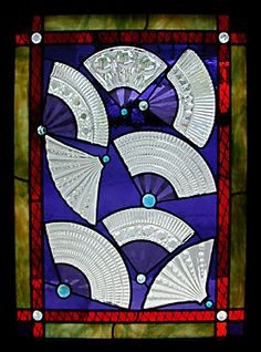 The fans are created with found glass objects from serving plates or bowls that were flattened in the kiln.   The rest of the glass in the piece is traditional stained glass with areas of added painted and fired decorations.
