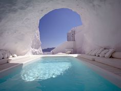 The Iconic Santorini Hotel in Imerovigli, Greece, has a pool that's embedded inside a cave. The cliffside overlooks the Mediterranean ocean.