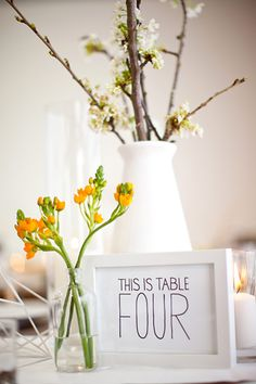 Hand drawn table numbers on white in a white frame on a white table in front of a white vase.