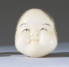 """IVORY MASK NETSUKE 20th Century Signed """"Tomogyoku"""". Depicting Okame. Length 1.6"""" (4 cm)."""