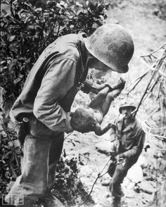 In a W. Eugene Smith photo that, somehow, captures both tenderness and horror, a U.S. Marine cradles a near-dead infant that the Marine found wedged, face down, literally under a rock while clearing out Japanese soldiers hiding in caves on Saipan, in the Mariana Islands. Hundreds of Japanese civilians in the islands committed suicide rather than surrender to the Americans.    see more — In Combat: LIFE's Great War Photographs 1944