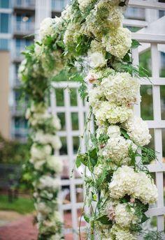 Garden-style white arbor, hydrangeas, greenery // Scobey Photography