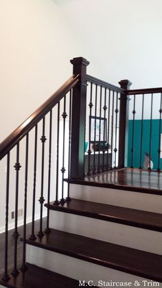 Staircase remodel from M.C. Staircase & Trim. Removal of carpet, wooden railing and wooden balusters. Installation of stained treads, risers, box newels, handrail, square rosettes and iron balusters. Iron balusters are the Twist Series Single twist and Versatile Double Knuckle in Satin Black.