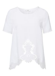 Polyester Broderie Hem Tee. Comfortable yet neat fitting A-line silhouette features a high scoop neck, short sleeves and dipped hem with front scallop edge and lace trims. Available in White as shown.
