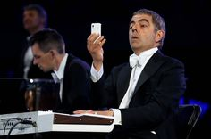 British actor Rowan Atkinson, in his role as Mr. Bean, takes pictures with his phone during a musical number in the Opening Ceremony. (Photo: Cameron Spencer / Getty Images)
