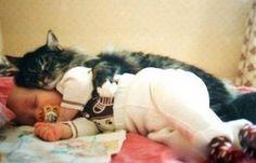 Ce Chat dort contre son petit maître tout bébé en ayant l'air de vouloir le protéger ...