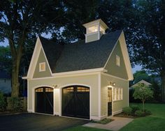 Traditional carriage house. This garage is so cute. Who would have thought to add a cupola to a garage? Wish I could see more of the house that goes with it!