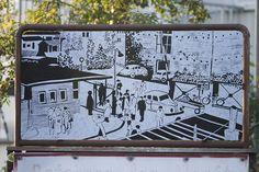 #Kiel Die Werft existiert nicht mehr, und das Gelände wird nun vom Ostuferhafen und von der Fachhochschule genutzt. Geblieben sind die beiden alten Schilder und die Erinnerung. Auch eine alte Fotografie aus den 1950er Jahren erinnert an die Vergangenheit und zeigt den Standort vor dem Bunker mit Passanten, Autos, Fahrrädern und einer offenen Schranke.