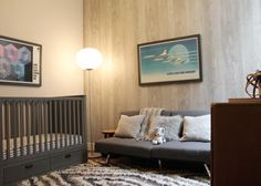This isn't your run-of-the-mill baby's room donned in pink or blue -- here's a space the parents will love, too! Bathed in grays and other neutral tones, the nursery boasts comfortable elements such as the couch with multiple, cozy throw pillows and lush shag rug. Graphic art posters bring bursts of color into the space.