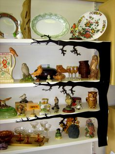 Showcasing Owl figurines with branches stuck onto the shelf edges. Creating interest in a difficult corner.