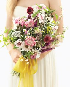 Chamomile, heather, white daisies, scabiosa, gooseneck loosestrife, raspberries, and wild sweetpeas mingle in a fresh-picked arrangement tied with a yellow bow