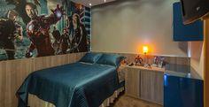 """O quarto projetado para um menino de 11 anos tem como tema o filme dos heróis """"Os Vingadores"""". Os tons de azul e revestimentos foram escolhidos para que, à medida que for crescendo, o menino não tenha que mudar radicalmente a decoração. Uma bancada para estudos em laca azul, mesmo tom do fundo do plotter dos heróis na parede, dá um toque colorido e alegra o quarto."""