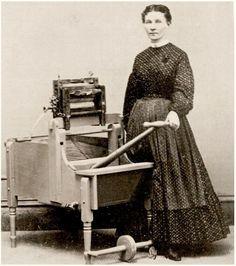 Woman wearing a print half apron with a Washing Machine in Watkins, N.Y. c. 1865…
