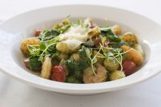 Gnocchi with shrimp, tomato, summer squash, rocket greens, and arugula pesto