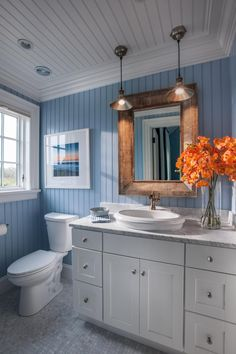 Artistic Touches  A locally-framed photograph of a Martha's Vineyard sunset successfully unifies the soothing blue and warm orange accents in this serene guest bathroom retreat.