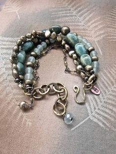 Four strands of beautiful moss cultured freshwater pearls, handmade aqua ceramic beads, and ocean wave prehnite, a tiny strand of brass, accented with brass Ethiopian trade beads and a handmade hammered brass clasp. A boho chic beauty. Bohemian bracelet, one of a kind.