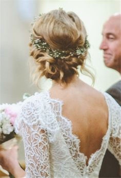 A Twisted Low Bun Wedding Hairstyle with Greenery and Flower Crown