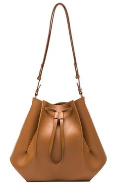 Large Bucket Bag by MAISON MARGIELA. Genuine leather with raw lining and silver-tone hardware. Made in Italy. Measures approx 10W x 12H x 6.5D. Adjustable shoulder strap. Drawstring opening. Interior pocket. Snap button closures along bottom. MMAR-WY50. S56WG0054 SY0327. Ab... #maisonmargiela #bags