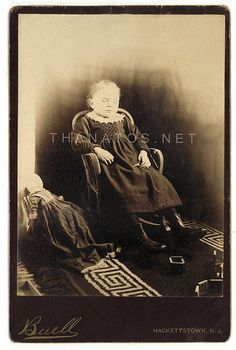 1880s cabinet card. The scissors are symbolic of death - basically, the cutting of the thread of life. It's also interesting to note that the doll's face is either completely covered or turned so that it is looking away from the girl.