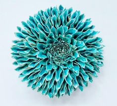 L'artiste Owen Mann is a self-taught sculptor from New York. Using porcelain and clay, the artist realizes series of flowers with dozens of petals, resembling peonies or dahlias. The common point of all his works is color, they are all simply painted in cold, blue or green tones.