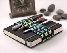 Journal Bandolier // space invaders // (a better pencil case, journal pen holder, book strap, pen lo Space Invaders, Cool Pencil Cases, Best Pencil, Silver Jewelry Cleaner, Black And White City, Book Journal, Journals, Pen Holders, Pencil Holder