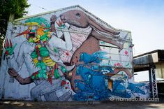 """""""His style is also very particular as he fills his murals with dressed up animal figures in surreal situations with a humorous twist"""" by @nomadbiba"""